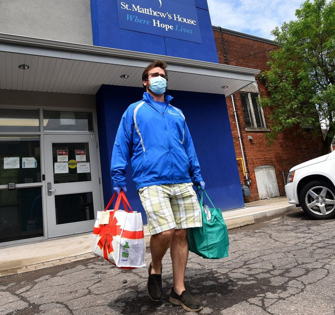 A man leaving the St. Matthew's building with groceries, wearing a mask